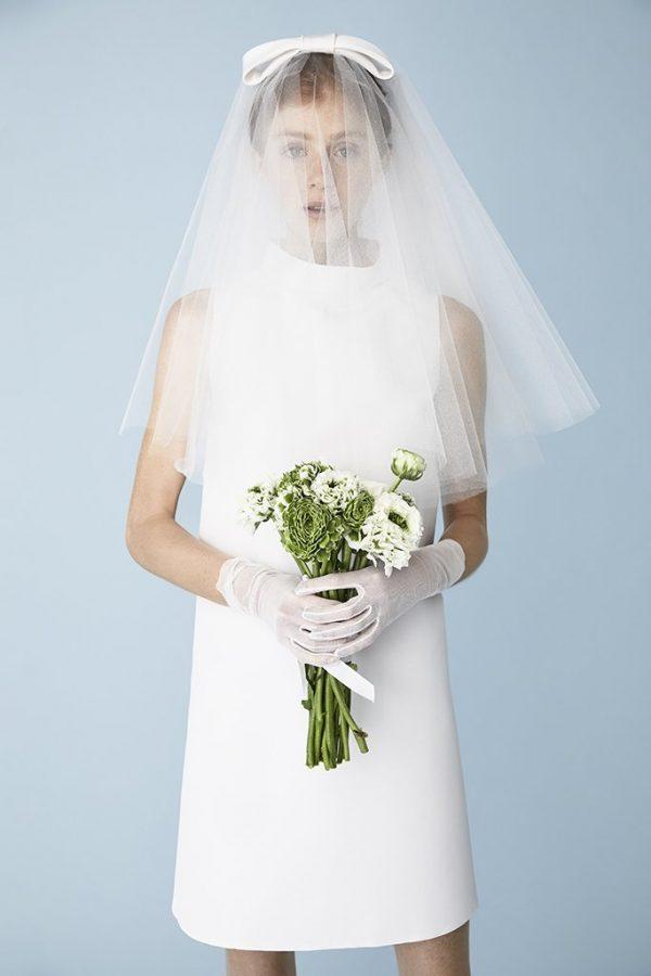 In questa foto una modella indossa un velo da sposa a petalo in tulle di seta con fiocco sul capo che le copre completamente il viso. Il velo è abbinato a un tubino e a dei guanti e porta tra le mani un bouquet di fiori di campo bianchi
