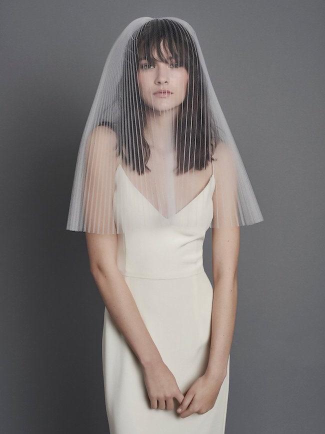 In questa foto una modella indossa un  abito bianco effetto lingerie e un velo da sposa a triangolo in tulle plissè