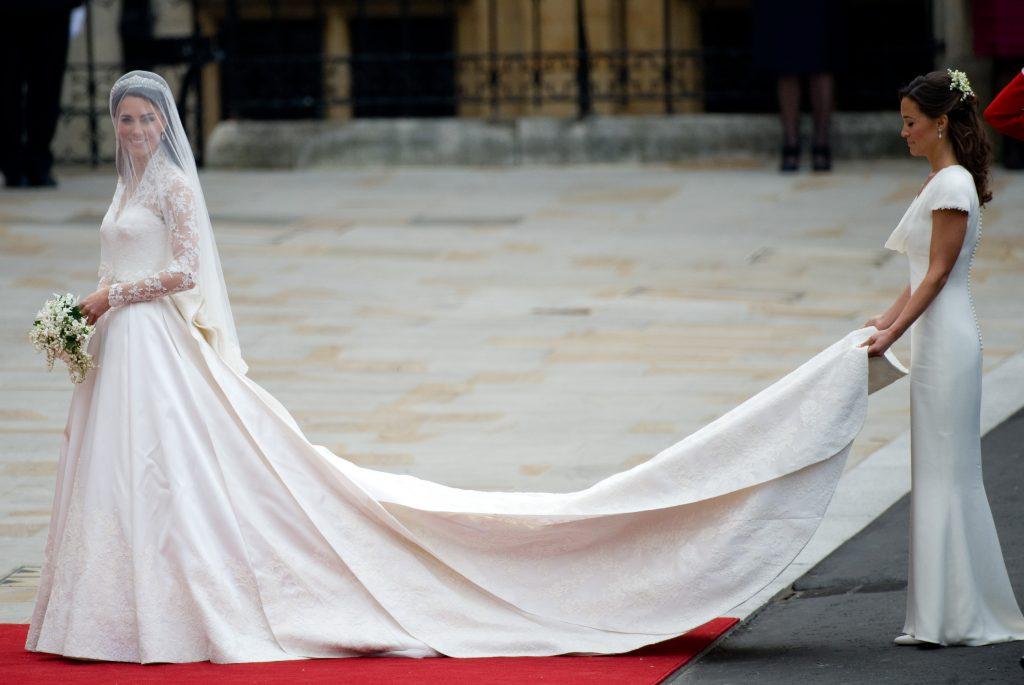 In questa foto Kate Middleton nel giorno del suo matrimonio prima di entrare nell'Abbazia di Westminster. Indossa un abito in taffetà con lungo strascico retto dalla sorella Pippa Middleton e maniche in pizzo con scollatura Queen Anne. Kate ha abbinato un velo ai fianchi in tulle con calata sotto il quale si intravede la tiara