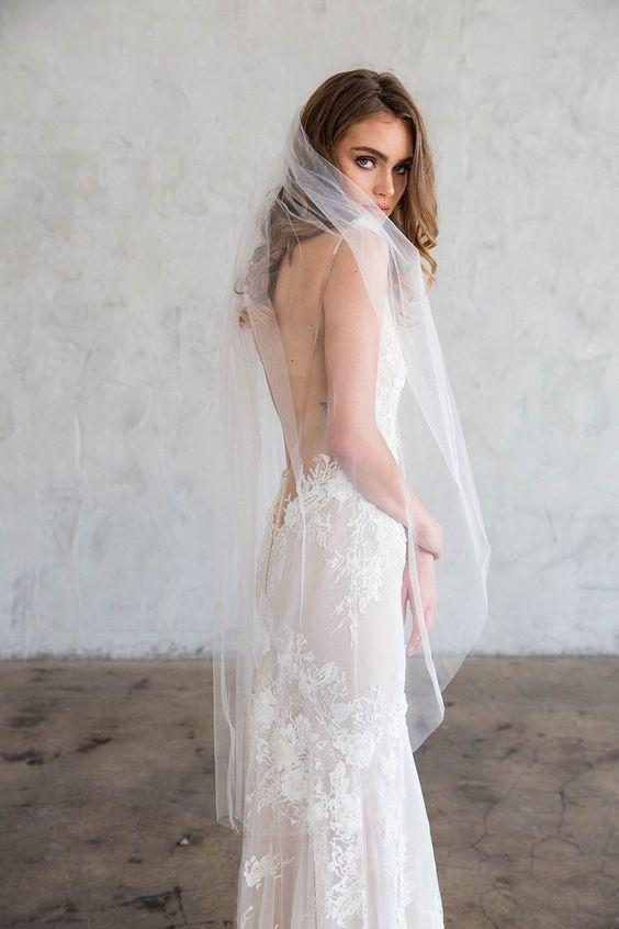 In questa foto una modella ritratta di profilo indossa un velo da sposa al ginocchio in tulle a taglio vivo abbinato ad un abito a sirena in pizzo e fondo rosa cipria