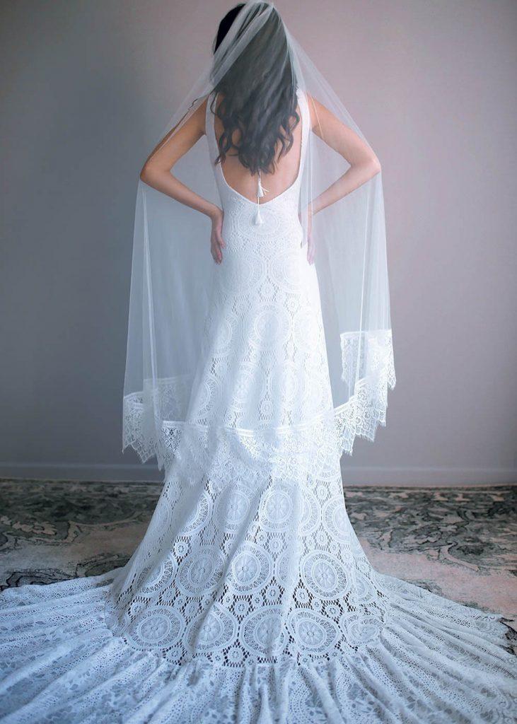 In questa foto una modella ritratta di spalle indossa un velo da sposa al ginocchio in tulle di seta con bordo in pizzo a tombolo