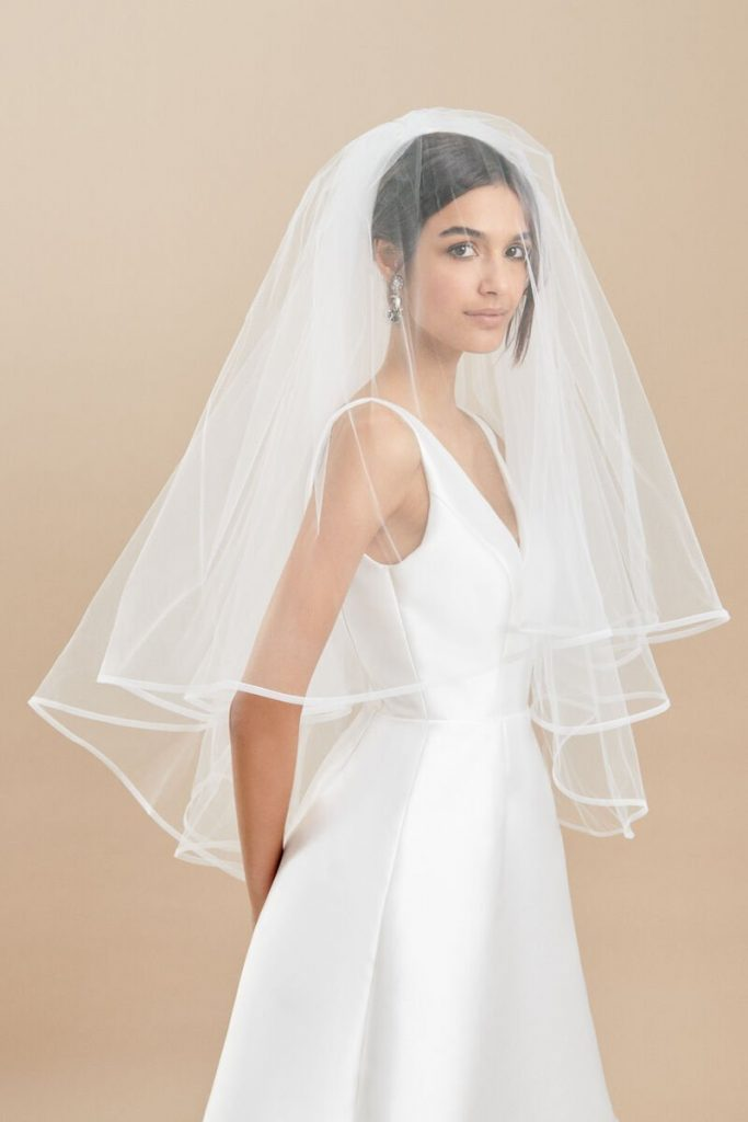 In questa foto una modella indossa un velo da sposa alla vita in tulle con bordo in raso e con calata