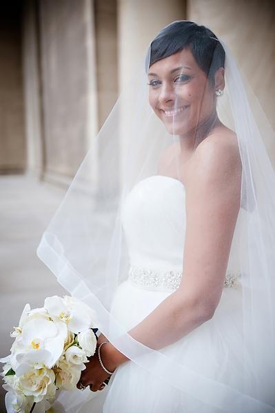 In questa foto una sposa indossa un velo alla vita con bordo largo in tulle e calata abbinato ad un abito con scollo a cuore. Porta tra le mani un bouquet di rose bianche e orchidee