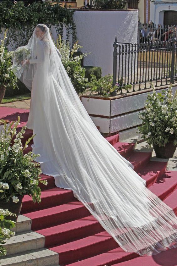In questa foto la modella Eva Gonzalez avvolta dal suo velo da sposa Cattedrale nel giorno delle sue nozze ritratta su una scalinata con tappeto rosso circondata da fiori bianchi