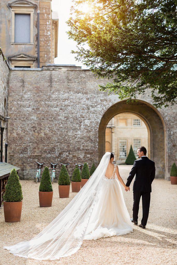 In questa foto due sposi che si guardano mentre camminano lungo il viale di un castello decorato con piante in vaso. La sposa indossa un abito ampio con schiena scoperta e un velo chiesa con bordo in pizzo fissato sul capo