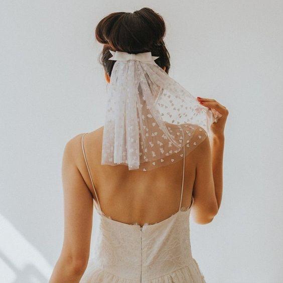 In questa foto una sposa ritratta di spalle indossa un velo corto con cuoricini fermato sotto lo chignon da un fiocco