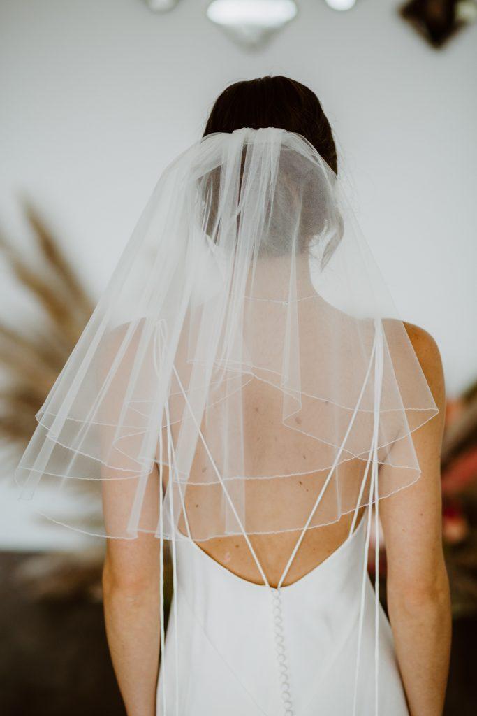 In questa foto una sposa indossa una velo Flyaway in tulle con bordino ricamato