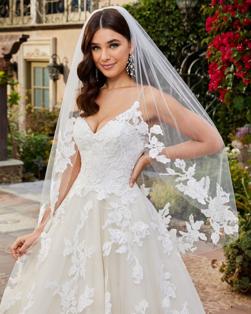 In questa foto una modella è ritratta nel giardino di una villa antica mentre indossa un abito da sposa ampio con corpetto in pizzo e ramage sulla gonna e un velo da sposa medio abbinato