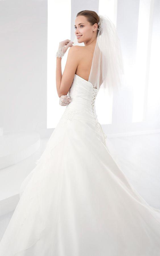 In questa foto una modella indossa un velo da sposa a scialle in tulle di seta e un abito da sposa in chiffon con corpetto chiuso sulla schiena da nastri. Il look è completato da guanti corti abbinati