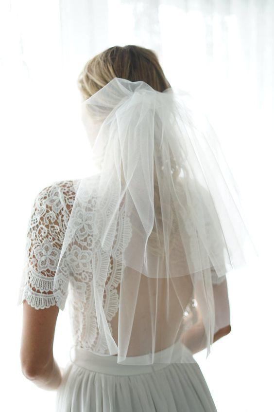 In questa foto una sposa con un velo a scialle in tulle con calata portata indietro e fermato a metà della nuca. La sposa indossa un abito in pizzo macramè scollato sulle spalle