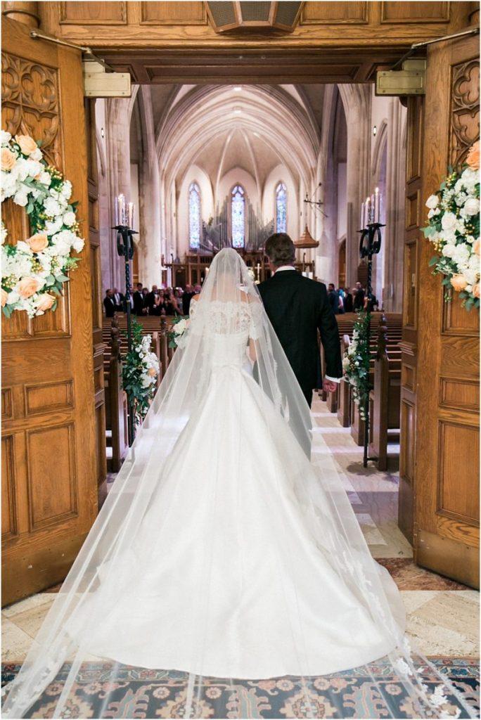 In questa foto una sposa mentre entra in chiesa al braccio del papà. Indossa un abito ampio in mikado con scollatura a barchetta in pizzo e un velo Cattedrale in tulle con bordo in pizzo abbinato