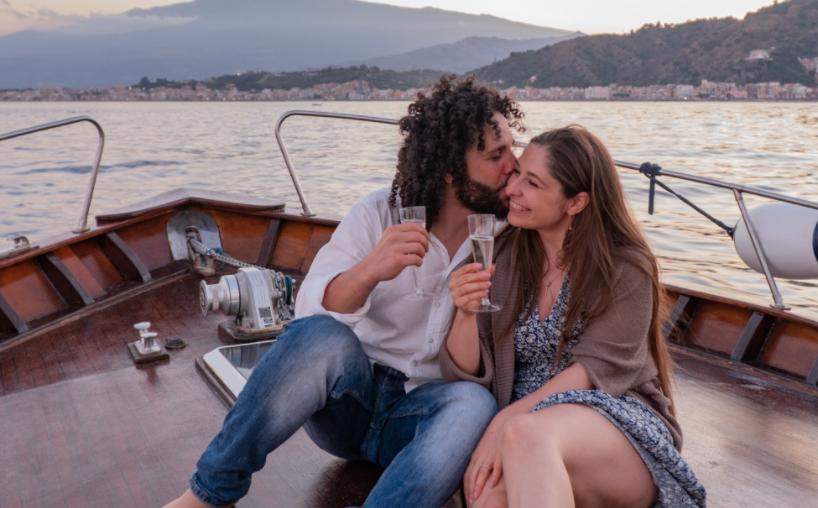 In questa foto i travel blogger Francesco e Veronica mentre brindano a bordo dell'imbarcazione su cui lui le ha fatto la proposta di matrimonio. Saranno i protagonisti del format Wed in Italy