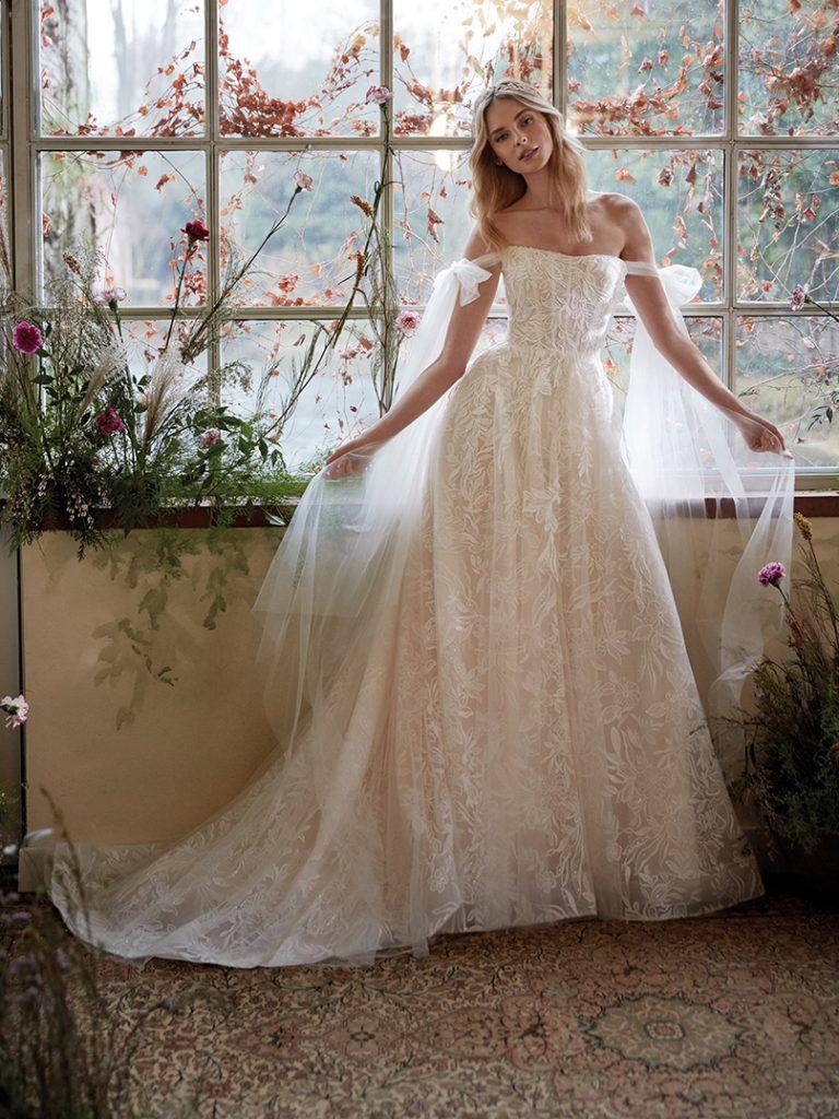 In questa foto un abito da sposa della collezione Nicole Colet 2022 con i veli che scendono dalle braccia