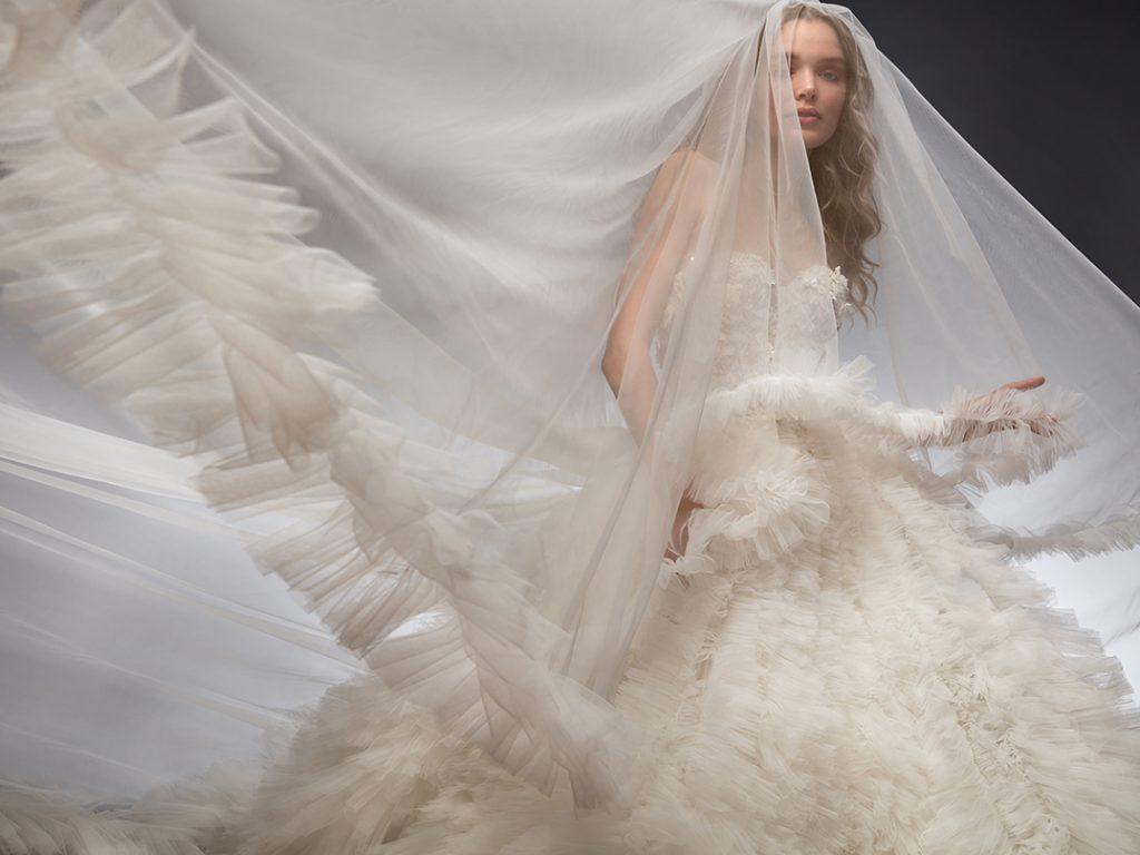 In questa foto un abito da sposa Nicole 2022 con ruches sull'intera gonna