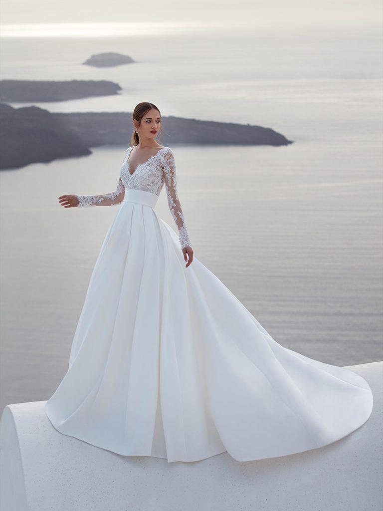 In questa foto un abito da sposa della collezione Nicole Jolies 2022 con corpetto in pizzo e gonna in seta