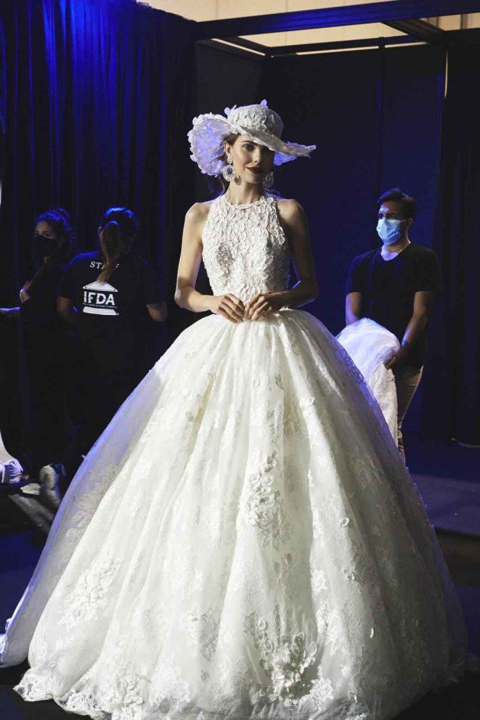 In questa foto un abito da sposa con corpetto in pizzo e ricami sulla gonna firmato dalla maison italiana