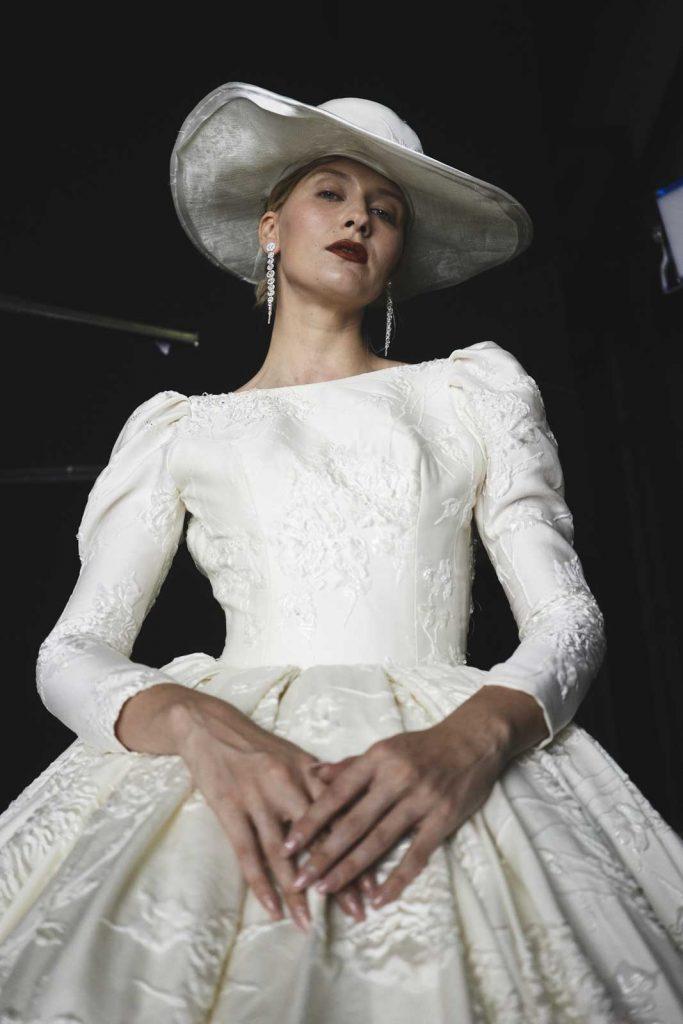 In questa foto un modello della collezione sposa 2022 di Amelia Casablanca con cappello e ricami in pizzo