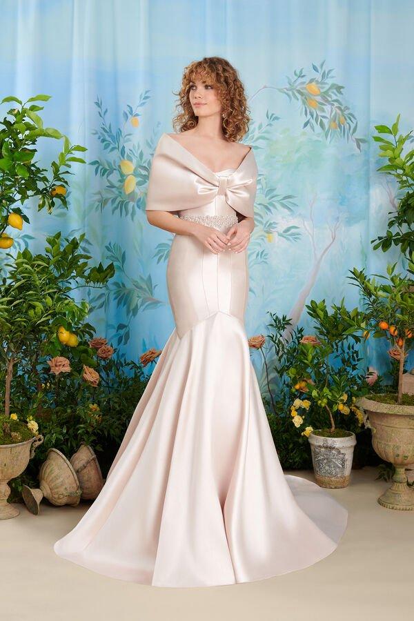 In questa foto una modella indossa un abito da sposa Atelier Emé avorio con copri spalle in mikado ton sur ton, drappeggiato davanti ad effetto fiocco