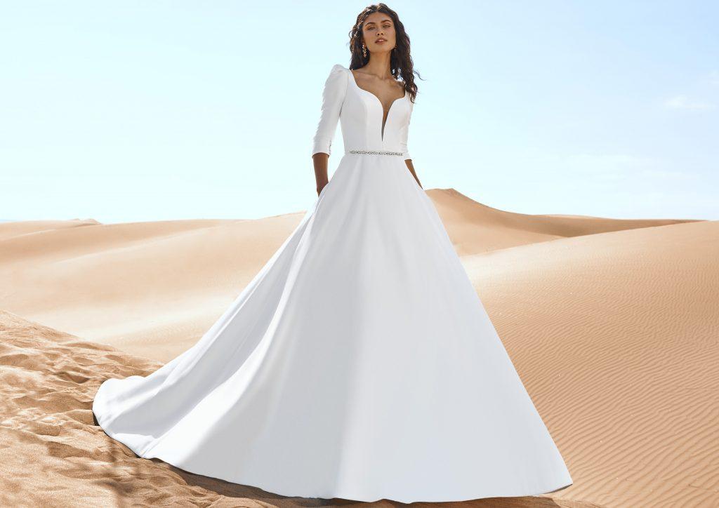 In questa immagine un modello con cintura preziosa della collezione di abiti da sposa Pronovias 2022
