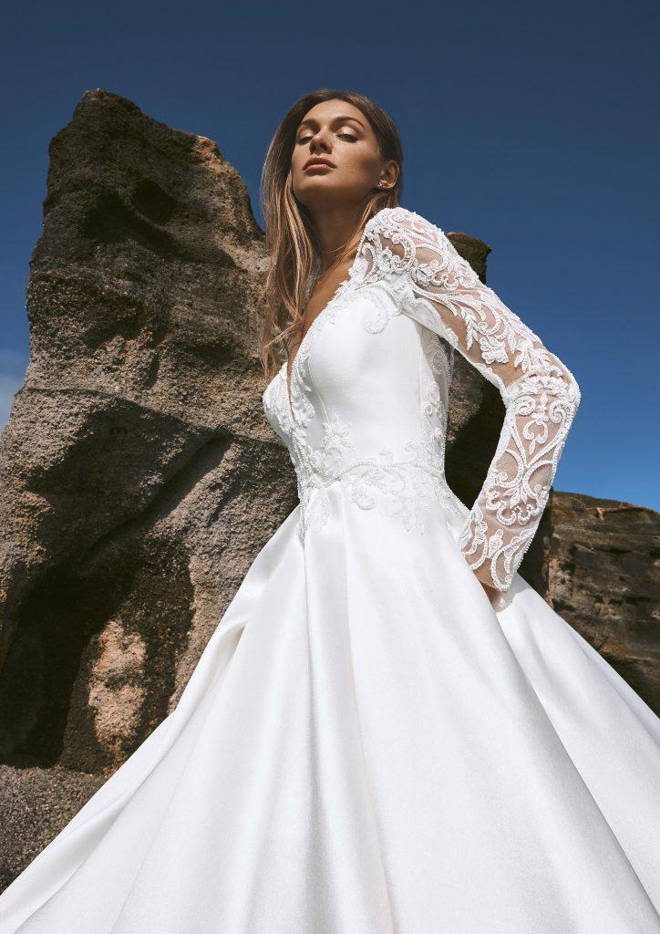 In questa immagine un modello maniche in pizzo della collezione di abiti da sposa Pronovias 2022