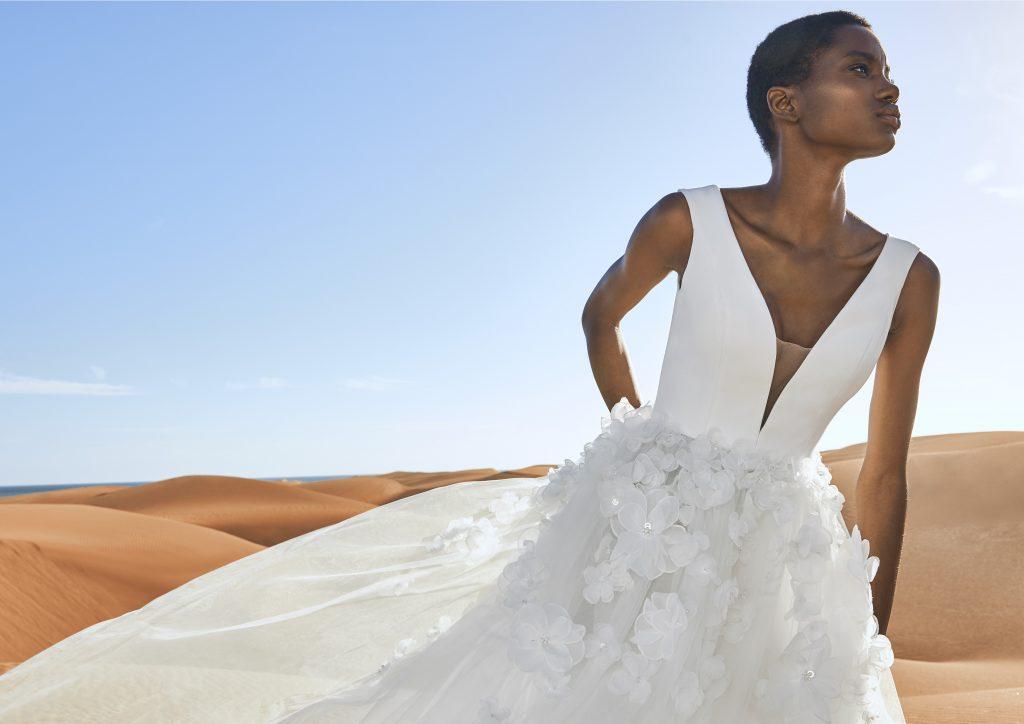 In questa immagine un modello con fiori in 3D sulla gonna della collezione di abiti da sposa Pronovias 2022