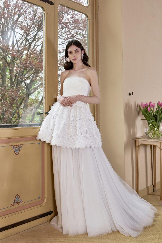 In questa foto una modella indossa un abito trasformabile della nuova collezione sposa carlo pignatelli 2022: è possibile rimuovere la parte inferiore della gonna e così il vestito diventa corto