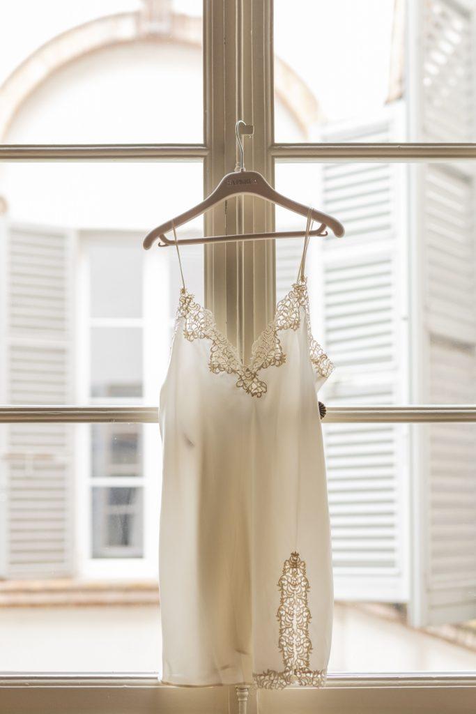 In questa foto una sottoveste bianca per la sposa di La Perla, in una gruccia appesa ad una finestra di un'abitazione