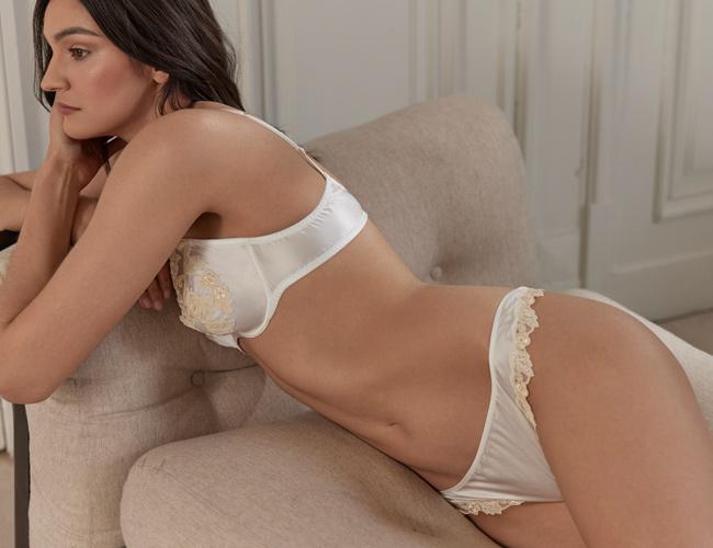 In questa foto una modella posa distesa su un divano in intimo da sposa La Perla, collezione Maison