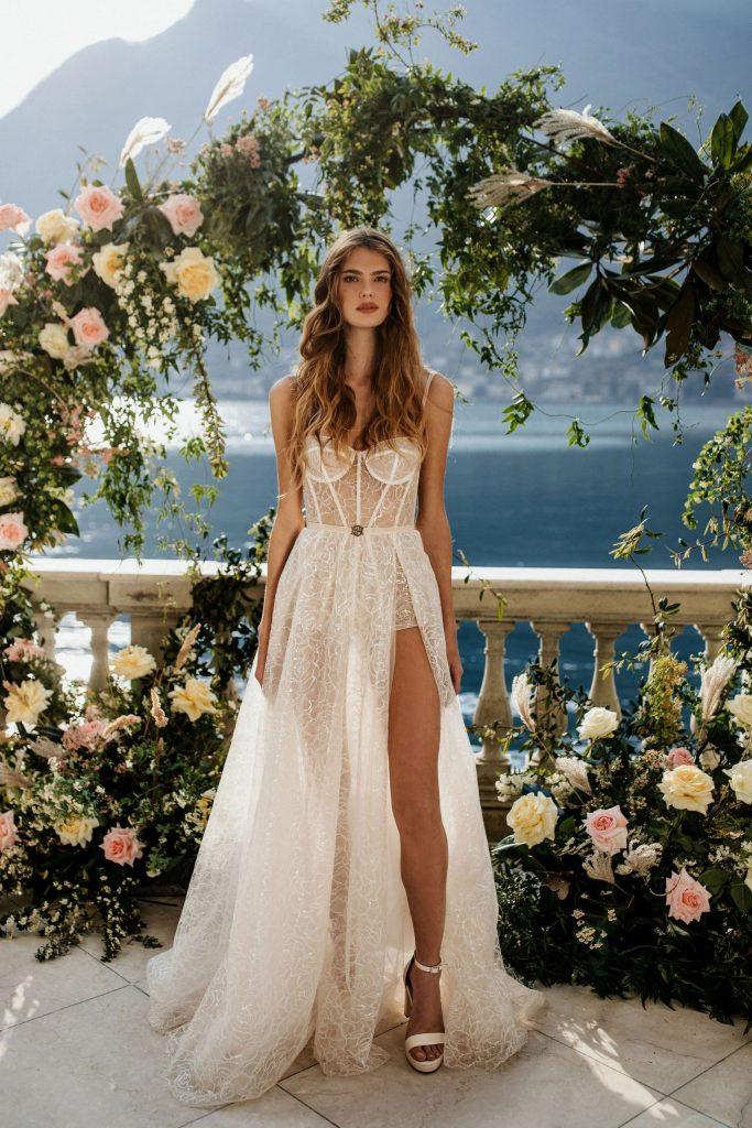 In questa foto una modella posa su una terrazza di fiori sul lago di Como indossando un abito da sposa per matrimonio civile in pizzo trasparente, corpetto steccato, shorts e spacco Muse by Berta