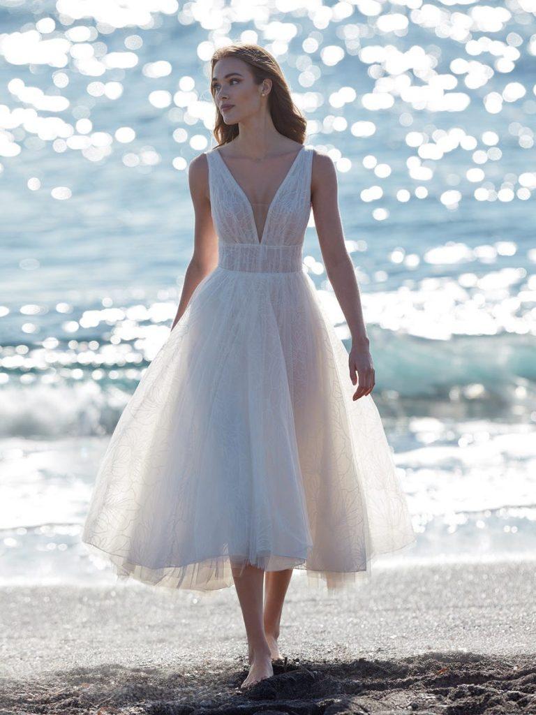 In questa foto una modella sulla spiaggia cammina indossando un abito da sposa midi per matrimonio civile in tulle glitter, scivolato e con scollatura a V firmato Nicole Milano  Collection
