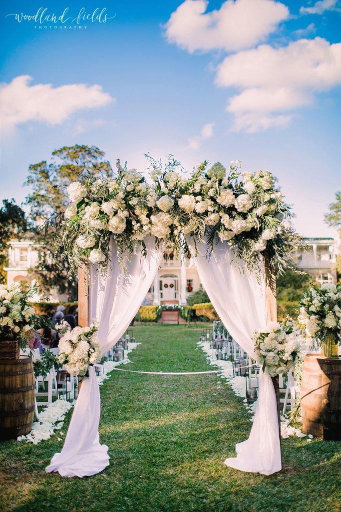 In questa foto l'allestimento di un matrimonio civile sul prato di una casa privata. Si apre con un arco decorato con stoffa e fiori bianchi. Ai lati sono poste delle botti di legno per vino