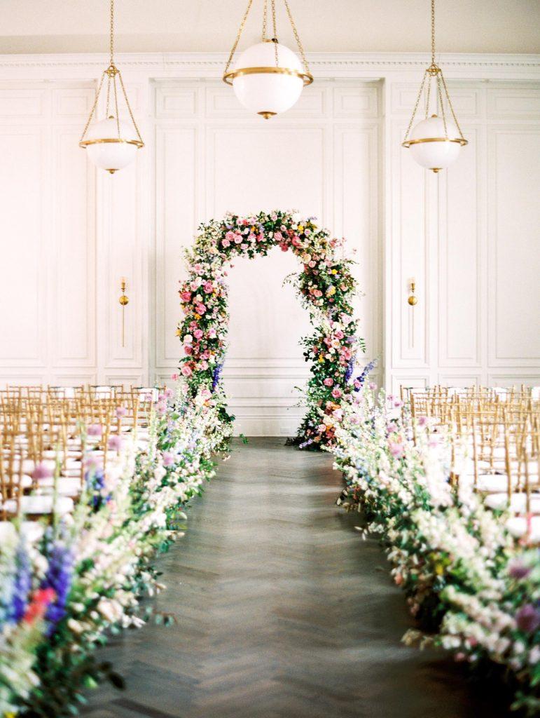 In questa foto l'allestimento di un matrimonio civile nella sala di una villa con sedie colore oro e bianche e composizioni di fiori di campo lungo il corridoio e che ricoprono interamente l'arco dove si celebrerà il rito