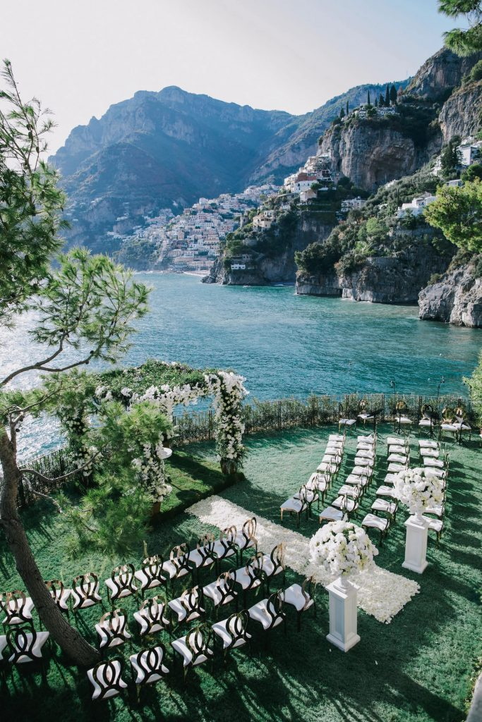 In questa foto l'allestimento di un matrimonio civile su un prato sul lago visto dall'alto.  Alla fine del semicerchio di sedie per gli ospiti è posto un gazebo interamente ricoperto di foglie e fiori bianchi