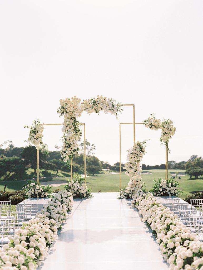 In questa foto un allestimento per un matrimonio civile in un campo da golf con fiori bianchi disposti lungo la navata. Alla fine del corridoio è presente una struttura di colore oro composta di rettangoli alti disposti ad incastro