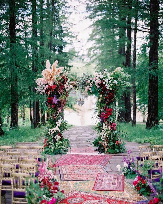 In questa foto l'allestimento floreale di un matrimonio civile in un bosco in stile etnico con tappeti lungo il corridoio centrale, sedie colore oro e viola e un arco di fiori rossi, viola e porpora