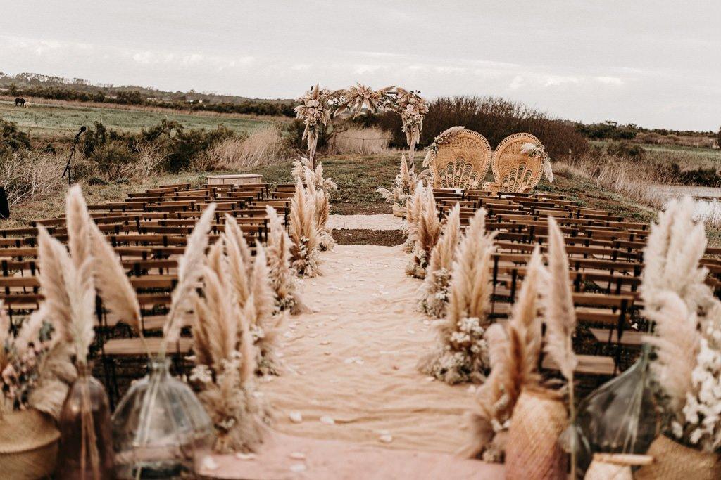 In questa foto l'allestimento di un matrimonio civile in un campo con pampas, ceste e vasi in vetro