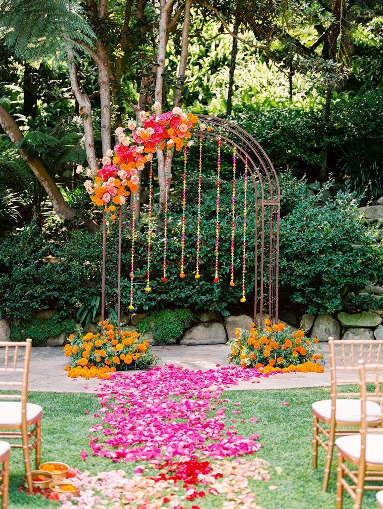 In questa foto l'allestimento di un matrimonio civile in giardino con fiori fuxia e arancioni. Al centro è presente un arco metallico con fiori pendenti come catenelle