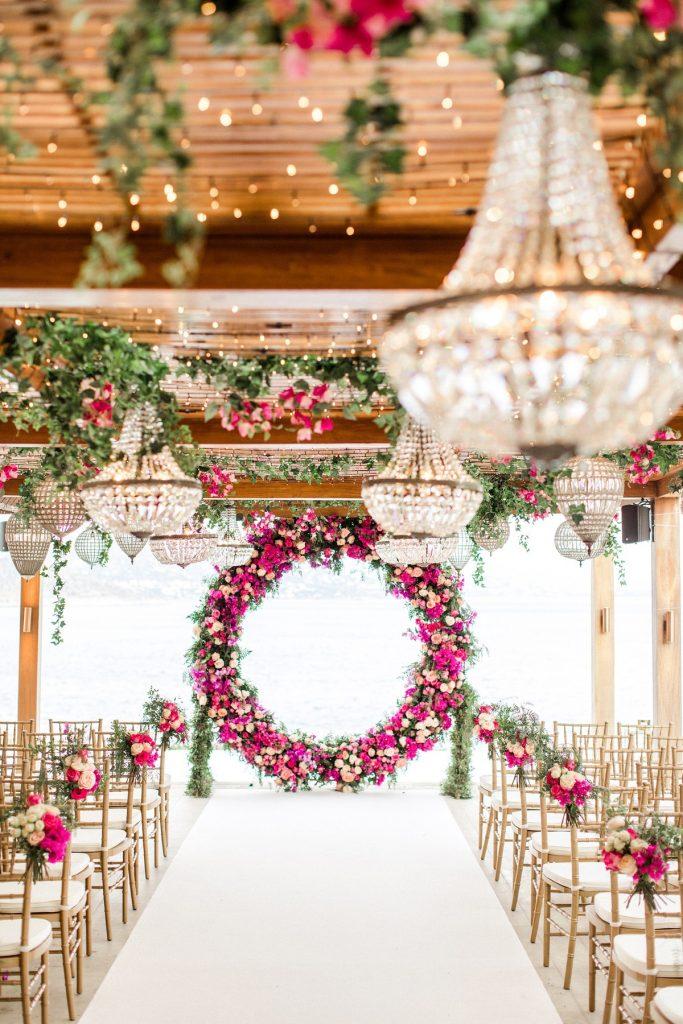 In questa foto l'allestimento floreale di un matrimonio civile sotto un grande patio di legno decorato con lampadari in cristallo e oro, sedie colore e bianco e fiori rosa e fuxia. Gli stessi fiori sono usati per decorare un arco circolare posto nel luogo del rito