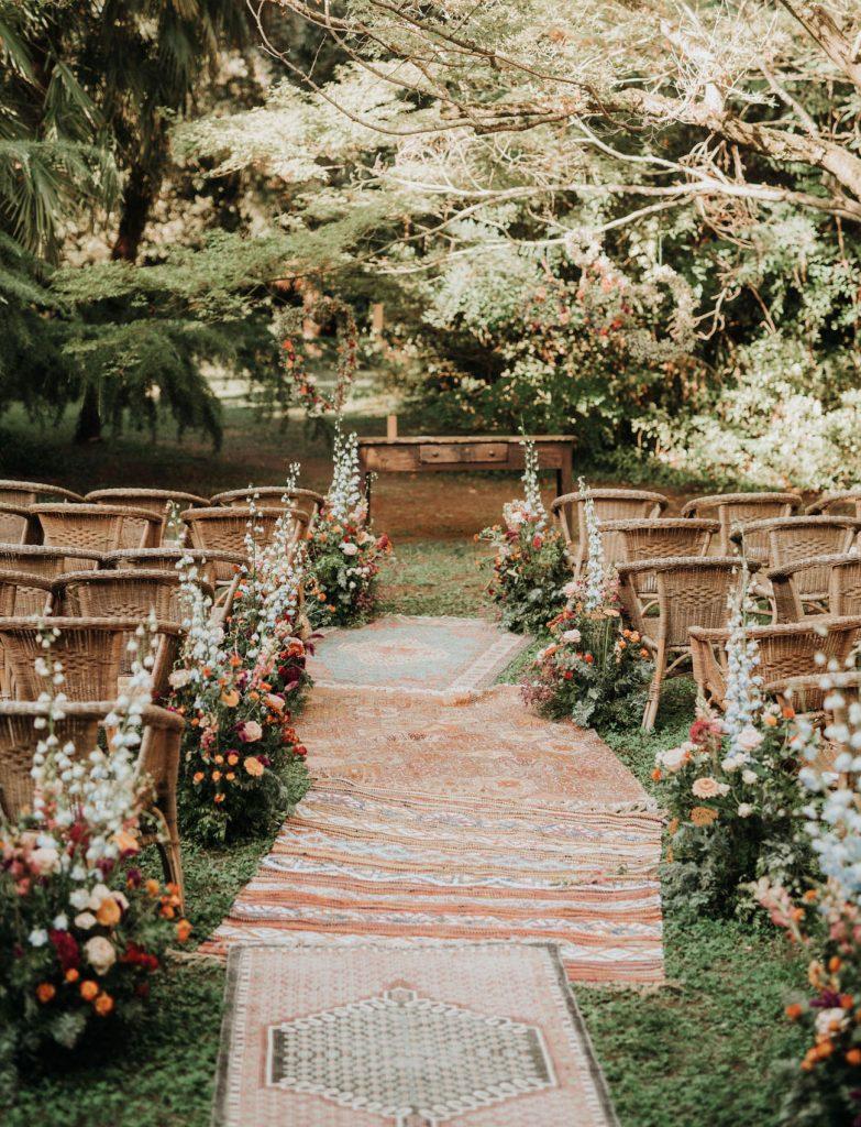 In questa foto l'allestimento di un matrimonio civile in stile vintage con antichi tappeti disposti lungo la navata, sedie in paglia, composizioni di fiori di campo e antica scrivania usata come luogo del rito