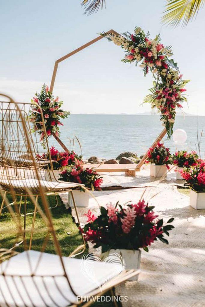 In questa foto l'allestimento di un matrimonio su un prato sul mare con fiori tropicali rosa e fuzia, sedie colore oro e un arco ottogonale decorato con fiori e palme