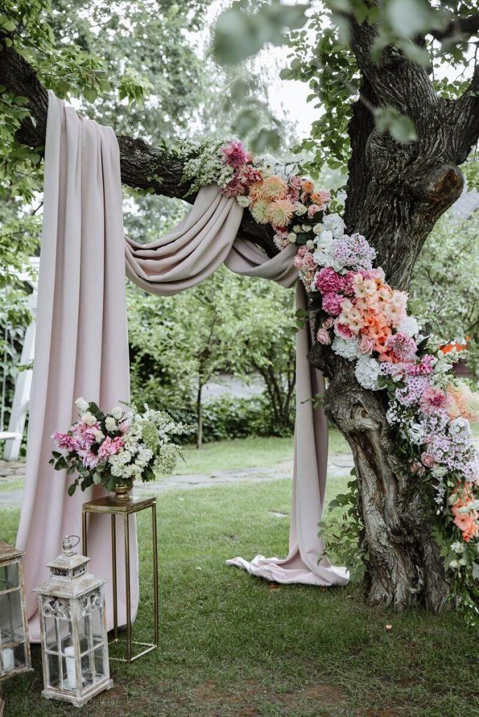 In questa foto un altare per matrimonio civile ricreato sotto un albero di ulivo decorato con drappi di stoffa rosa pallido e fiori fuxia, bianchi rosa pesca. A terra sono disposte alcune lanterne e alzatine dorate