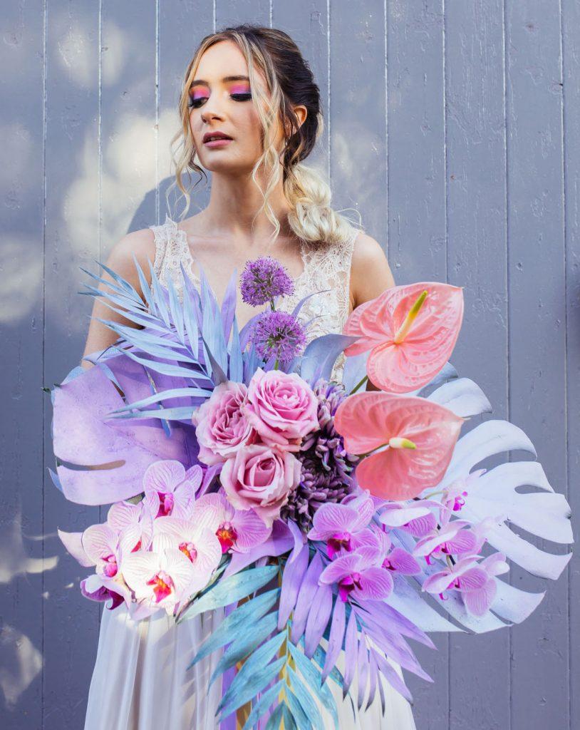 In questa foto una sposa posa con il suo bouquet multicolor dai toni del rosa e dele viola con palme, rose, orchidee e piante grasse