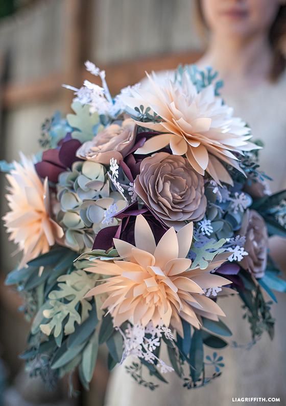 In questa foto un bouquet da sposa per matrimonio civile con fiori di carta nei toni del verde, del pesca e del bordeaux