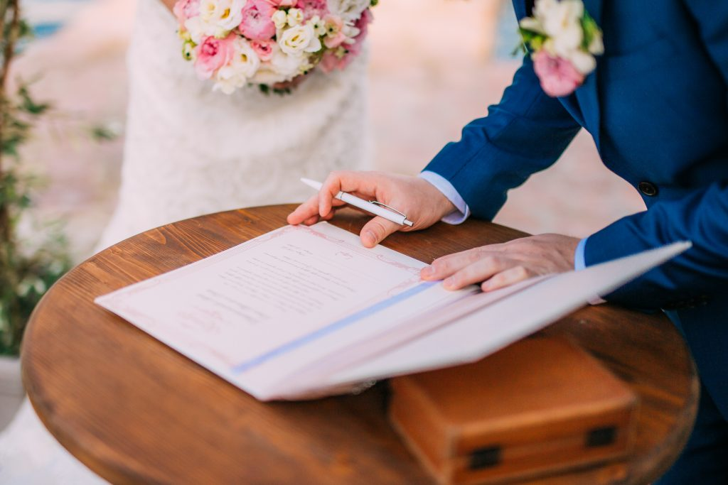 In questa foto sono inquadrate le mani di due sposi. Lo sposo sta firmando i documenti delle nozze civili su un tavolino di legno mentre la sposa lo guarda tenendo un bouquet di fiori rosa e bianchi