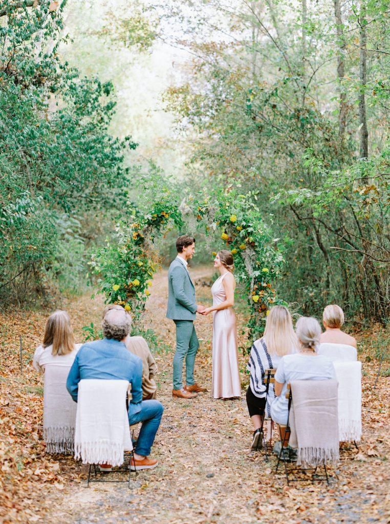 In questa foto due sposi in un bosco davanti ad un arco di foglie e fiori gialli si scambiano le promesse davanti a 6 invitati durante il loro elopement wedding