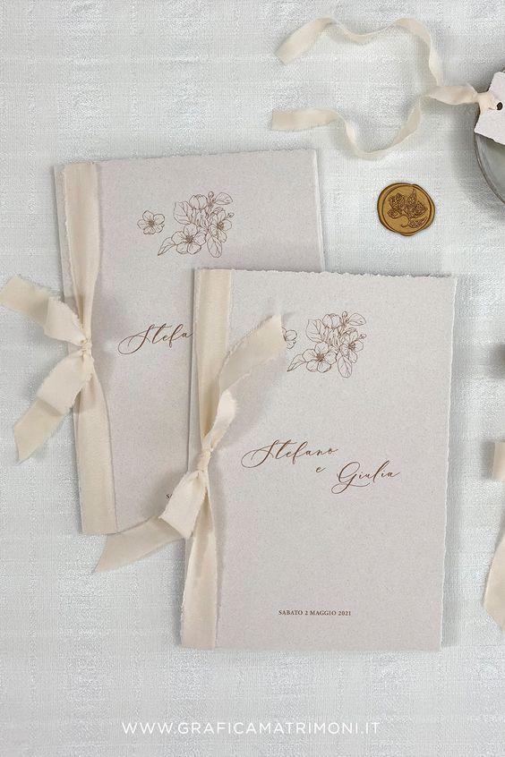 In questa foto due libretti per matrimonio civile nei colori del bianco e del panna con decori floreali in alto