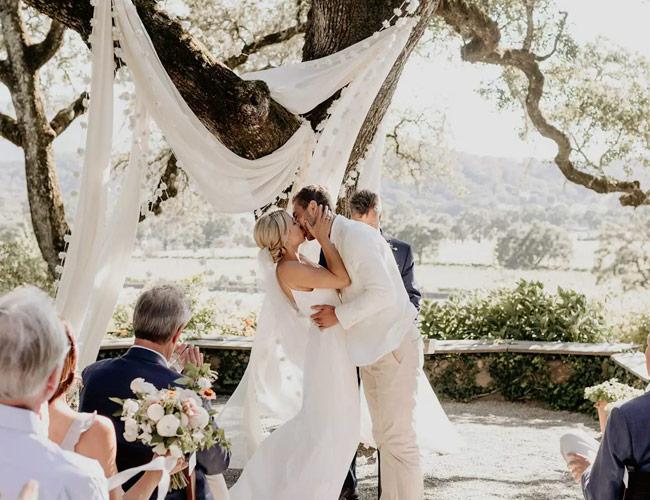 In questa foto due sposi si baciano al termine del loro matrimonio civile celebrato sotto una tenda di lino bianca in un campo di ulivi. Gli ospiti gli applaudono