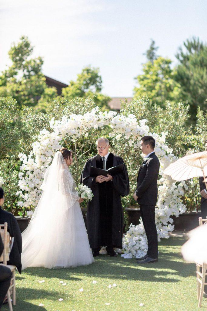 In questa foto l'officiante del matrimonio civile celebra il rito su un prato. Davanti a lui lo ascoltano i due sposi. Dietro di loro è stato allestito un cerchio di fiori bianchi
