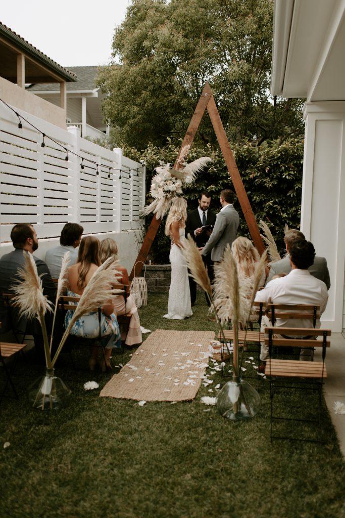 In questa foto un matrimonio civile celebrato su un giardino di casa in stile boho chic. L'allestimento è realizzato con pampas e un triangolo di legno posto dietro all'officiante al posto del tavolo di nozze. Gli sposi si tengono per mano mentre i pochi invitati assistono alla cerimonia