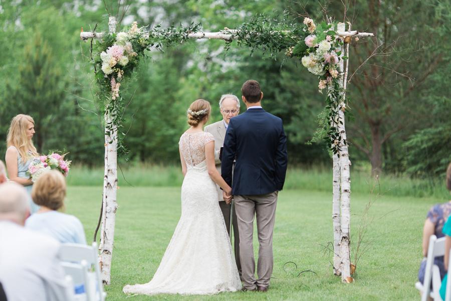 In questa foto due sposi ascoltano il celebrante durante il loro matrimonio civile organizzato su un prato sotto un arco di legno decorato con fiori bianchi e rosa